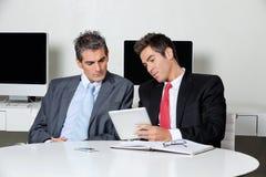 Hombres de negocios usando la tableta de Digitaces en el escritorio fotos de archivo
