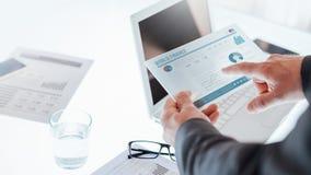 Hombres de negocios usando un dispositivo de la pantalla táctil Fotos de archivo libres de regalías