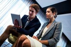 Hombres de negocios usando una tableta Fotos de archivo