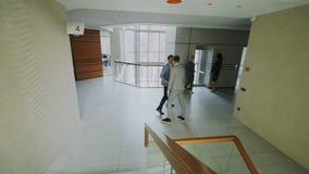 Hombres de negocios y el caminar y reunión de los colegas del busineswoman en centro moderno de la oficina dentro