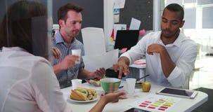 Hombres de negocios y empresaria Having Working Lunch en oficina almacen de metraje de vídeo