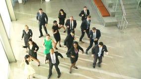 Hombres de negocios y empresarias que bailan en pasillo de la oficina almacen de video