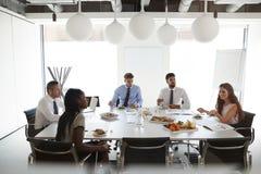Hombres de negocios y empresarias que se encuentran en la sala de reunión moderna sobre almuerzo de funcionamiento imagen de archivo