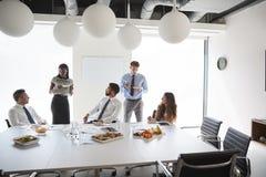 Hombres de negocios y empresarias que se encuentran en la sala de reunión moderna sobre almuerzo de funcionamiento imágenes de archivo libres de regalías