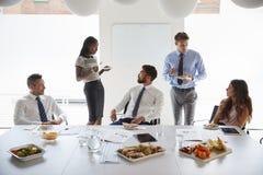 Hombres de negocios y empresarias que se encuentran en la sala de reunión moderna sobre almuerzo de funcionamiento fotos de archivo