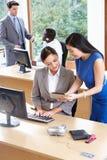Hombres de negocios y empresarias que trabajan en oficina ocupada Imágenes de archivo libres de regalías