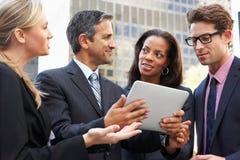 Hombres de negocios y empresarias que usan la tableta de Digitaces afuera fotos de archivo