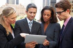 Hombres de negocios y empresarias que usan la tableta de Digitaces afuera Foto de archivo