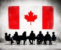 Hombres de negocios y la bandera nacional de Canadá Imagen de archivo