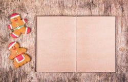 Hombres de pan de jengibre y un libro con las páginas en blanco Fondo de papel Galletas del día de fiesta Imagen de archivo