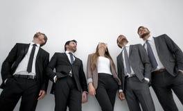 Hombres de una mujer tres en los trajes de negocios que se colocan en fila Imagen de archivo libre de regalías