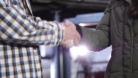 Hombres del apretón de manos, mecánico de automóviles y muchachas del cliente en la gasolinera almacen de metraje de vídeo