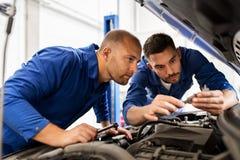 Hombres del mecánico con la llave que repara el coche en el taller fotos de archivo libres de regalías