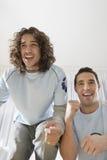 Hombres emocionados que miran la televisión Imagen de archivo libre de regalías