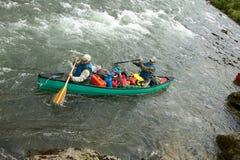 Hombres en canoa sobrecargada en rápidos remotos del río Imágenes de archivo libres de regalías