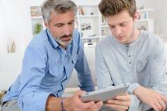 Hombres en casa con la tableta Imagen de archivo libre de regalías