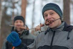 Hombres en comida campestre en madera Imagen de archivo libre de regalías