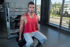 Hombres en el gimnasio que ejercitan el bíceps con pesas de gimnasia Imágenes de archivo libres de regalías