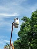 Hombres en el trabajo, luz de la lámpara del arreglo en el camino Fotos de archivo libres de regalías