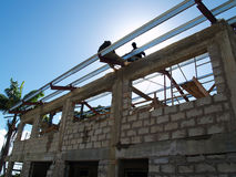 Hombres en el trabajo que construye el tejado en un edificio concreto imagen de archivo