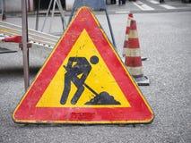 Hombres en la señal de tráfico del trabajo Imagen de archivo libre de regalías