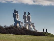 Hombres en las estatuas colosales del mar en el mar de wadden en Esbjerg, Dinamarca fotos de archivo