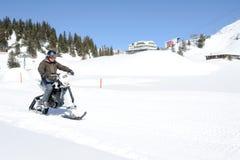 Hombres en moto de nieve en Engelberg en las montañas suizas Imagen de archivo libre de regalías