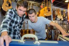 Hombres en tienda del instrumento musical Fotos de archivo
