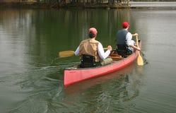 Hombres en una canoa imagenes de archivo