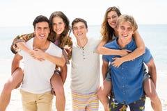 Hombres felices que llevan a cuestas a mujeres en la playa Fotografía de archivo