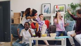 Hombres felices y mujeres con las banderas canadienses que miran deporte en la TV que celebran la victoria metrajes