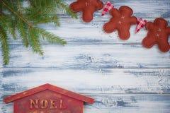 Hombres hechos a mano del jengibre, ramas de árbol de navidad, casa de Noel en fondo de madera Fotografía de archivo libre de regalías