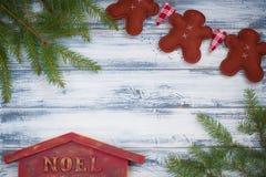 Hombres hechos a mano del jengibre, ramas de árbol de navidad, casa de Noel en fondo de madera Imagenes de archivo