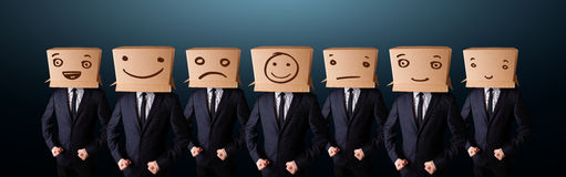 Hombres hermosos en traje que gesticulan con las caras sonrientes exhaustas en la caja Imagen de archivo libre de regalías