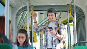 Hombres hermosos jovenes que disfrutan de viaje en el transporte público, colocándose con el auricular mientras que se mueve en l almacen de video