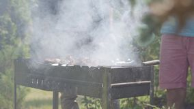 Hombres irreconocibles que hacen el Bbq en el primer del jardín Ocio del verano Amigos que cocinan la carne en la parrilla almacen de video