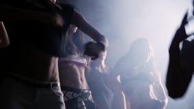 Hombres jovenes alegres del partido del golpeador y muchachas calientes que bailan en sitio oscuro metrajes