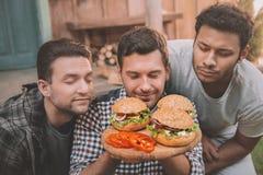 Hombres jovenes con los ojos cerrados que huelen las hamburguesas hechas en casa frescas Imágenes de archivo libres de regalías
