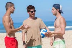 Hombres jovenes en la playa que sostiene la bola Foto de archivo libre de regalías