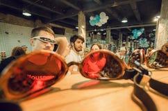 Hombres jovenes en los vidrios divertidos que se divierten dentro de la tienda de las gafas de sol Imágenes de archivo libres de regalías