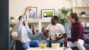 Hombres jovenes felices que celebran meta durante el partido de f?tbol en hacer de la TV alto-cinco metrajes