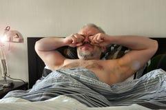 Hombres jovenes hermosos Despertó mañana en cama y frota sus ojos imagen de archivo libre de regalías