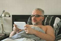 Hombres jovenes hermosos despertó por la mañana y lee las noticias imagen de archivo libre de regalías