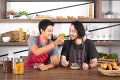 Hombres jovenes hermosos que desayunan junto, un cereal forrajero del hombre al otro en el apartamento moderno del comedor el fin foto de archivo