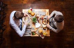 Hombres jovenes que almuerzan en un café Fotos de archivo