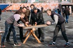 Hombres jovenes que asierran un tronco de árbol en una diversión tradicional del día de fiesta en C Fotografía de archivo libre de regalías
