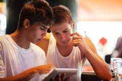 Hombres jovenes que buscan en Internet con el cojín adentro Imagenes de archivo