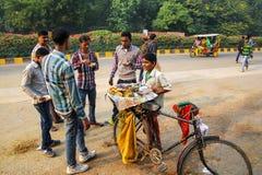 Hombres jovenes que comen el bocado indio del chaat en la vecindad o de Taj Ganj Foto de archivo