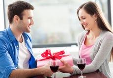 Hombre que da el regalo de la mujer en el café Foto de archivo