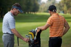 Hombres jovenes que defienden en campo de golf la bolsa de golf por completo de palillos imágenes de archivo libres de regalías